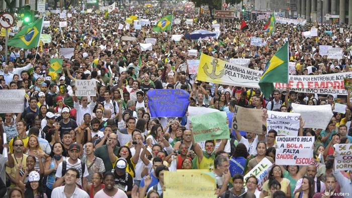 Demonstrators hoild a protest in Rio de Janeiro, one of many such protests in Brazil's major cities, June 20, 2013. Tens of thousands of demonstrators marched through the streets of Brazil's biggest cities on Thursday in a growing protest that is tapping into widespread anger at poor public services, police violence and government corruption. The signs reads, Wake up Brazil, As the football rolls, we're missing health and schools, and Hospital of FIFA standard. REUTERS/Luciana Whitaker (BRAZIL - Tags: CIVIL UNREST POLITICS) / Eingestellt von wa