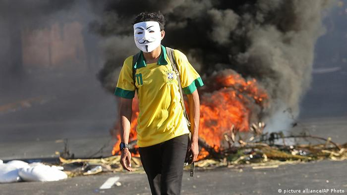 This June 19, 2013 photo, a masked protester walks away from a burning barricade near the Castelao stadium in Fortaleza, Brazil.(AP Photo/Andre Penner, File)