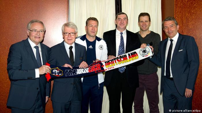 Horst R. Schmidt, Reinhard Rauball, Andreas Köpke, Daniel Nivel, Oliver Bierhoff und Wolfgang Niersbach halten einen Fußballschal hoch. (Foto: EPA/Markus Gilliar / POOL, dpa)