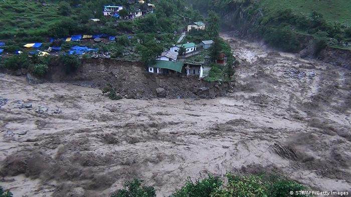 Houses perch precariously as river banks collapse from the rising waters of the flooded river in the northern state of Uttarakhand on June 17, 2013. (Photo: STR/AFP/Getty Images)