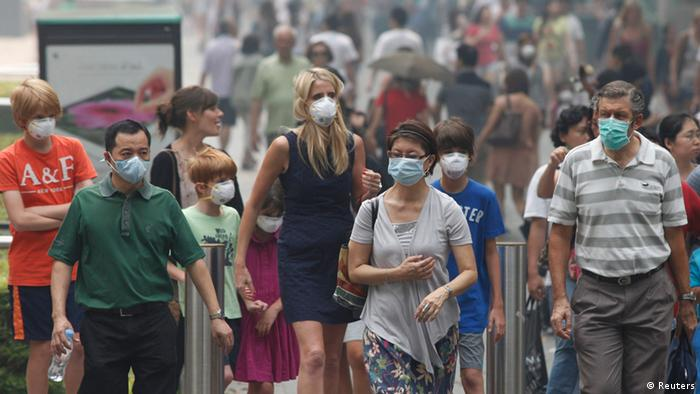 People wearing masks cross a street in Singapore's Orchard Road shopping area June 21, 2013. The haze blanketing Singapore from fires in Indonesia could persist for weeks or even longer, Prime Minister Lee Hsien Loong said on Thursday, warning of consequences if Singapore-linked companies were found responsible for the burning. REUTERS/Edgar Su (SINGAPORE - Tags: ENVIRONMENT HEALTH)