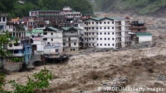 Fast moving water from the Alaknanda river destroys building during a heavy monsoon rain in Govindghat town in the Indian state of Uttrakhand on June 17, 2013. Heavy rains lashed parts of north India Monday, resulting in the deaths of at least 18 people, as the annual monsoon covered the country nearly two weeks ahead of schedule, officials said. More than a dozen people lost their lives due to record downpours in Uttarakhand state, situated in the foothills of the Himalayas, a local official said. AFP PHOTO/ STR (Photo credit should read STRDEL/AFP/Getty Images)