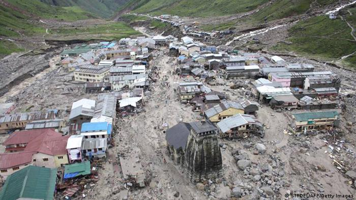 The Kedarnath Temple (C, foreground) is pictured amid flood destruction in the holy Hindu town of Kedarnath, located in Rudraprayag district in the northern Indian state of Uttarakhand, on June 18, 2013. Torrential rains washed away hundreds of homes and roads, leaving at least 64 people dead and thousands stranded, after the annual monsoon hit northern India earlier than expected, officials said June 18. AFP PHOTO/STR (Photo credit should read STRDEL/AFP/Getty Images)