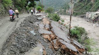 People walk along a damaged road after heavy rains in the Himalayan state of Uttarakhand June 17, 2013(Photo: REUTERS/Stringer)
