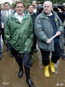 ** FILE ** German Chancellor Gerhard Schroeder, left, and Saxony state governor Georg Milbradt wear rubber boots as they walk in the mud of a flood-striken street in Grimma, eastern Germany, in this Aug. 14 2002 file photo. Three years ago, a beleaguered Chancellor Gerhard Schroeder donned rubber boots to head the fight against disastrous floods in east Germany, railed against war in Iraq and rode to an unexpected knife-edge victory with the help of eastern support. A raft of unpopular reforms later, Schroeder now faces a much tougher sell in eastern towns like Magdeburg, a drab, economically depressed state capital, ahead of Sept. 18 national elections. (AP Photo/Eckehard Schulz)