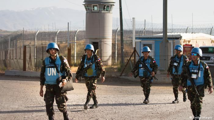 GOLAN HEIGHTS - JUNE 12: (ISRAEL OUT) Filipino Peacekeepers of the United Nations Disengagement Observer Force (UNDOF) cross the Quneitra crossing from Syira into Israel, as a first group of Austrian troops moved today from Syria into Israel, with their disengagement is expected to be completed within weeks, on June 12, 2013 in Golan Heights. The Austrian force has patrolled the buffer zone between Israel and Syria as part of the United Nations Disengagement Observer Force, known as UNDOF, since it was set up in 1974. (Photo by Uriel Sinai/Getty Images)