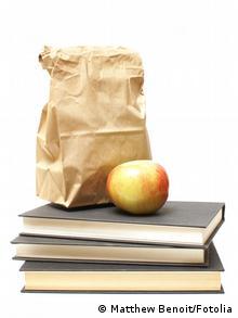Eine Papiertüte und ein Apfel liegen auf einem Stapel Bücher (Foto: Fotolia/Matthew Benoit)