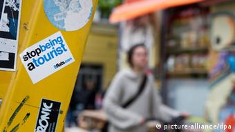 Urban symbolic photo of Berlin, front in focus on sticker that says 'stop being a tourist,' back is blurry Photo: picture-alliance/dpa