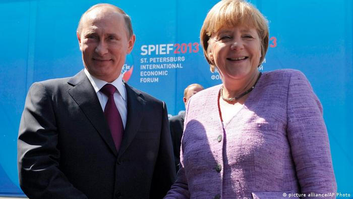 Russian President Vladimir Putin, left, and German Chancellor Angela Merkel shake hands during their meeting at the economic forum in St. Petersburg, Russia, Friday, June 21, 2013. (AP Photo/RIA-Novosti, Mikhail Klimentyev, Presidential Press Service)