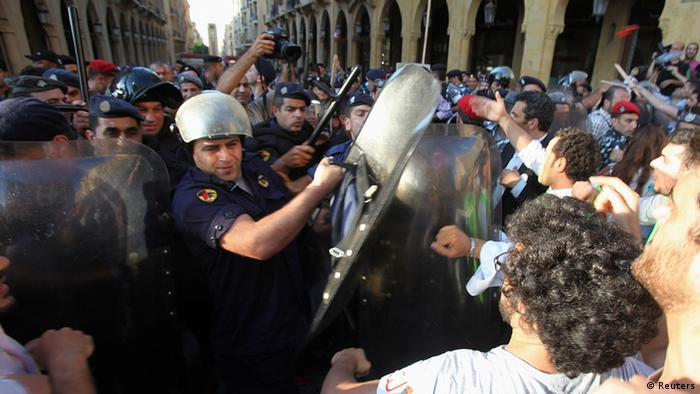 Activists and members of civil society organizations scuffle with Lebanese anti-riot policemen blocking their way to reach parliament building during protest against extension of parliament terms in Beirut