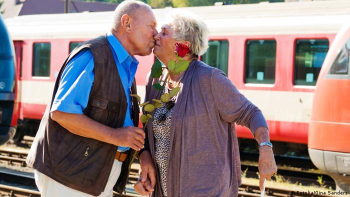 An elderly couple kiss at a train station (Photo: Gina Sanders)