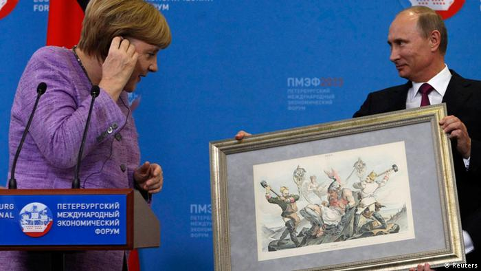 Russia's President Vladimir Putin (R) presents a historical lithograph to Germany's Chancellor Angela Merkel during a news conference after their meeting at the St. Petersburg International Economic Forum in St. Petersburg, June 21, 2013. REUTERS/Alexander Demianchuk (RUSSIA - Tags: BUSINESS POLITICS)