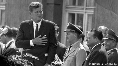 John F. Kennedy legt die Hand auf seine linke Brust