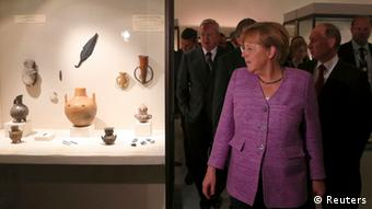Russia's President Vladimir Putin (front R) and Germany's Chancellor Angela Merkel (front L) visit the State Hermitage Museum in St. Petersburg, June 21, 2013. Putin dismissed a report on Friday that he cancelled a visit to the museum with Merkel where she was due to refer to German art seized by the Soviets in the wake of World War Two. REUTERS/Anatoly Maltsev/Pool (RUSSIA - Tags: POLITICS)
