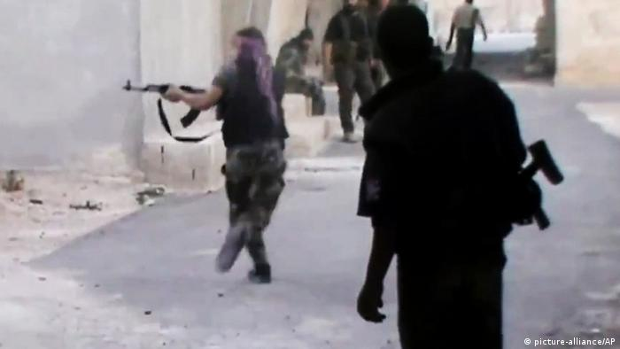 In this image taken from video obtained from the Shaam News Network, which has been authenticated based on its contents and other AP reporting, a Free Syrian Army fighter runs for cover during clashes with government forces, not pictured, in the Damascus suburb of Dhiyabieh, Syria, on Thursday, June 20, 2013. (AP Photo/Shaam News Network via AP video)