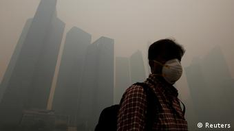 A man wearing a mask walks past the skyline of Singapore's business district, which has been blanketed in haze, as the Pollutant Standards Index (PSI) climbs up to 401 at 12pm (0400 GMT), June 21, 2013. (Photo: Reuters)