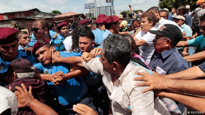An elderly man hits a police officer at during a demonstration in Nicaragua