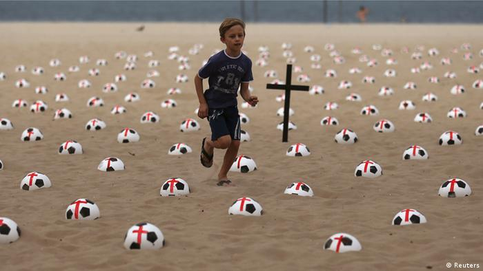 A boy runs among soccer balls marked with red crosses as a protest on Copacabana beach in Rio de Janeiro June 22, 2013. Copyright: REUTERS/Pilar Olivares