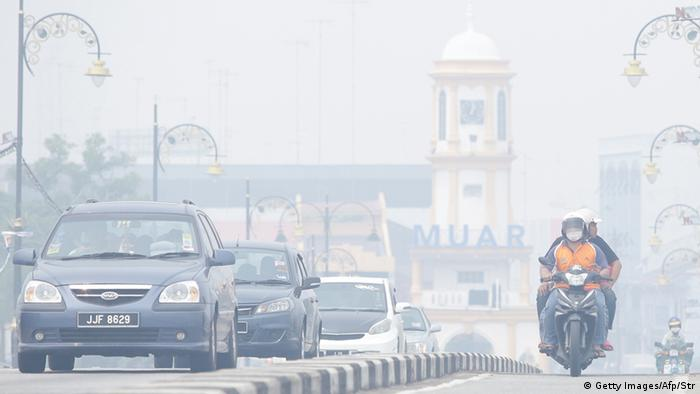 Motorists drive as haze covers Muar city in Muar, southern Malaysia on June 23, 2013. The thick smog brought on by forest fires in Indonesia has choked parts of southern Malaysia, prompting environment officials to push for an emergency on June 23. AFP PHOTO (Photo credit should read STR/AFP/Getty Images)
