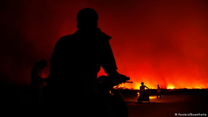 Villagers sit on their motorcycles as they get ready to leave their homes as a fire burns a palm oil plantation in the Bangko Pusako district in Rokan Hilir, in Indonesia's Riau province June 22, 2013. Indonesia's environment minister said eight domestic firms were suspected of being responsible for the blazes on Sumatra island that blanketed neighboring Singapore in record levels of hazardous smog. The parent companies of the Indonesian firms included Malaysia-listed Sime Darby and Singapore's Wilmar Group. Singapore has warned the haze - which has fuelled fears about health problems and raised diplomatic tension in Singapore, Malaysia and Indonesia - could last for weeks, or even longer. REUTERS/Beawiharta (INDONESIA - Tags: DISASTER ENVIRONMENT HEALTH TPX IMAGES OF THE DAY)