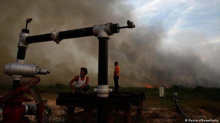 Villagers rest on an oil well as a fire burns a palm oil plantation at the haze hit Bangko Pusako district in Rokan Hilir, in Indonesia's Riau province June 22, 2013. Indonesia's environment minister said eight domestic firms were suspected of being responsible for the blazes on Sumatra island that blanketed neighboring Singapore in record levels of hazardous smog. The parent companies of the Indonesian firms included Malaysia-listed Sime Darby and Singapore's Wilmar Group. Singapore has warned the haze - which has fuelled fears about health problems and raised diplomatic tension in Singapore, Malaysia and Indonesia - could last for weeks, or even longer. Photo: REUTERS / Beawiharta