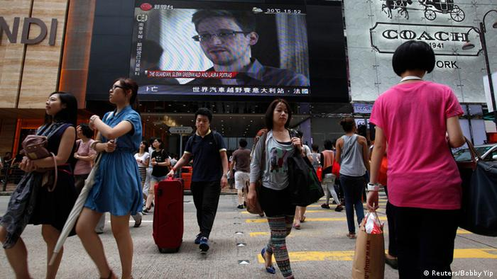 People cross a street in front of a monitor showing file footage of Edward Snowden, a former contractor for the U.S. National Security Agency (NSA), with a news tag (L) saying he has left Hong Kong, outside a shopping mall in Hong Kong June 23, 2013. (Photo: REUTERS/Bobby Yip)