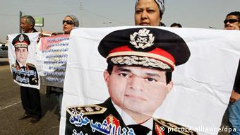 epa03605799 Egyptian Pro-military forces protesters hold posters depicting Egyptian Minister of Defense Abdel-Fattah al-Sissi, during a demonstration against the Muslim Brotherhood, in front of the Tomb of the Unknown Soldier in Nasr City Cairo, Egypt,01 March 2013. The protest is a call to keep the military free of Brotherhood influence so that President Mohamed Morsy's government can't use the Armed Forces as a tool to attack peaceful protesters. EPA/KHALED ELFIQI