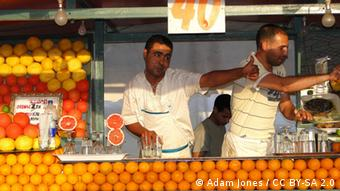 Two men on a beach sell juice at a stand covered in oranges(Foto: Adam Jones / CC BY-SA 2.0)