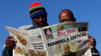 Men read a newspaper next to a stall in Soweto June 24, 2013. South Africans appeared resigned on Monday to the inevitability of one day saying goodbye to former president Nelson Mandela after the 94-year-old anti-apartheid leader's condition in hospital deteriorated to critical. REUTERS/Siphiwe Sibeko (SOUTH AFRICA - Tags: POLITICS HEALTH)