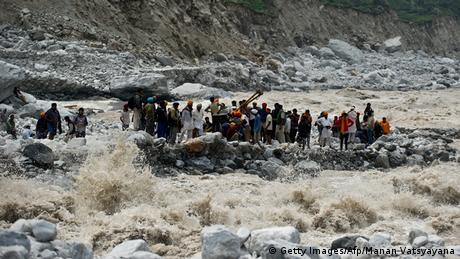 Indo-Tibetan Border Police (ITBP) personnel and local residents pull a rope to rescue stranded pilgrims on the other side of a river at Govind Ghat on June 23, 2013. (Photo: AFP)