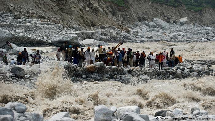 Indo-Tibetan Border Police (ITBP) personnel and local residents pull a rope to rescue stranded pilgrims on the other side of a river at Govind Ghat on June 23, 2013. Rescue operations have intensified in northern India where up to 1,000 people are feared to have died in landslides and flash floods that have also left pilgrims and tourists stranded without food or water for days. AFP PHOTO/MANAN VATSYAYANA (Photo credit should read MANAN VATSYAYANA/AFP/Getty Images)