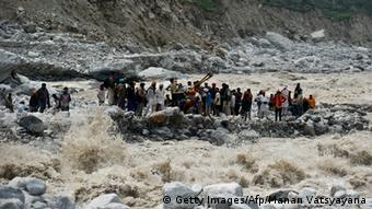 Indo-Tibetan Border Police (ITBP) personnel and local residents pull a rope to rescue stranded pilgrims on the other side of a river at Govind Ghat on June 23, 2013(Photo: MANAN VATSYAYANA/AFP/Getty Images)