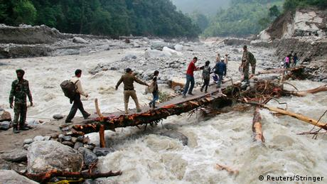 Indian army personnel help stranded people cross a flooded river after heavy rains in the Himalayan state of Uttarakhand June 23, 2013. (Photo: Reuters
