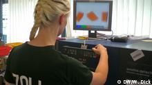 Monitor lässt erkennen, wo Drogen versteckt sind. Foto: DW/Wolfgang Dick, Redaktion Deutschland Hintergrund Mitarbeiterin des Zolls am Flughafen Frankfurt kontrolliert Päckchen am Spezial-Detektor