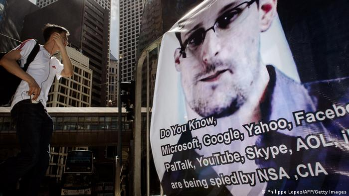 A man walks past a banner displayed in support of former National Security Agency contractor Edward Snowden (c) PHILIPPE LOPEZ/AFP/Getty Images