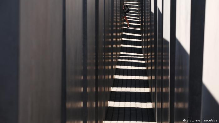Im Holocaust-Denkmal Berlin: Die Sonne scheint hinein und die verschiedenen Stelen werfen ihre Schatten. I Hintergrund links geht eine Frau zwischen zwei Stelen durch.