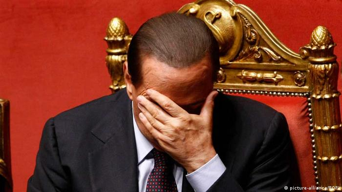 Silvio Berlusconi holds his hand over his face while seated (c) picture-alliance/ROPI