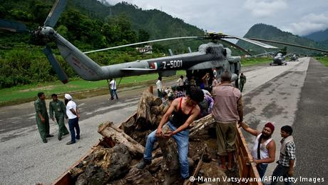 Indian workers offload wood, to be carried to Kedarnath by the Indian Air Force (IAF) for cremation preparations, at Gauchar Airfield in Uttarakhand state on June 25, 2013. (Photo: AFP)