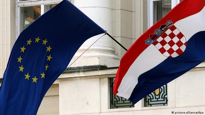 A Croatian national flag (R) and a European Union flag (L) in front of the government building in Zagreb
