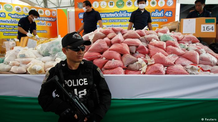 REFILE - CORRECTING '42ND' A policeman guards bags of methamphetamine pills during the 42nd Destruction of Confiscated Narcotics ceremony in Ayutthaya province, nearly 80 km (50 miles) north of Bangkok, June 26, 2013. More than 3.3 tons (6600 pounds) of drugs, including methamphetamine, marijuana, heroin and opium, worth more than $333 million, were destroyed as the Thai government began its anti-drug campaign, according to the Thai Ministry of Public Health. REUTERS/Chaiwat Subprasom (THAILAND - Tags: DRUGS SOCIETY CRIME LAW)