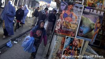 Bollywood and Hollywood Posters pasted on the video shop as local passes by in Kabul Afghanistan,Tuesday, Dec. 21, 2004. There's vitality, even impatience for things to get on in Kabul, from the culinary scene to the shops doing brisk business on bootleg DVDs and CDs after a ban on music and television during the hardline Taliban regime. (AP Photo/Rafiq Maqbool)