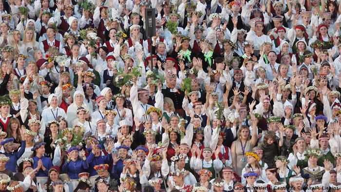 Big crowd photo at a singing festival, participants are dressed in national Latvian costumes, Photo: A. Liepins