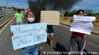 A little group of demonstrators attempt to block the road from the airport to the city in Belo Horizonte, on June 26, 2013 a few hours ahead of the Brazil vs Uruguay game. Brazil is currently facing unprecedented social unrest, marked by almost daily street protests to demand better public services and an end to rampant political corruption, the protests come as Brazil hosts a dry run for the World Cup, called the Confederations Cup. AFP PHOTO / CHRISTOPHE SIMON (Photo credit should read CHRISTOPHE SIMON/AFP/Getty Images)