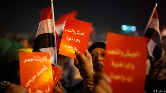 Protesters hold soccer red cards while chanting anti-Mursi and anti-Muslim Brotherhood slogans as they wait in Tahrir square ahead of President Mohamed Mursi's public address, in Cairo June 26, 2013. The cards read, Red card, go out! REUTERS/Asmaa Waguih (EGYPT - Tags: POLITICS CIVIL UNREST)