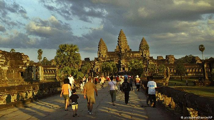 Tourists walk to the world famous Angkor Wat temple in the late afternoon light in Siem Reap, 330 km's (220 miles) northwest of Phnom Penh Friday Dec 9, 2005. Tourist numbers to Cambodia topped 1 million in 2004 and have risen to 1.3 million in 2005. (AP Photo/Andy Eames)