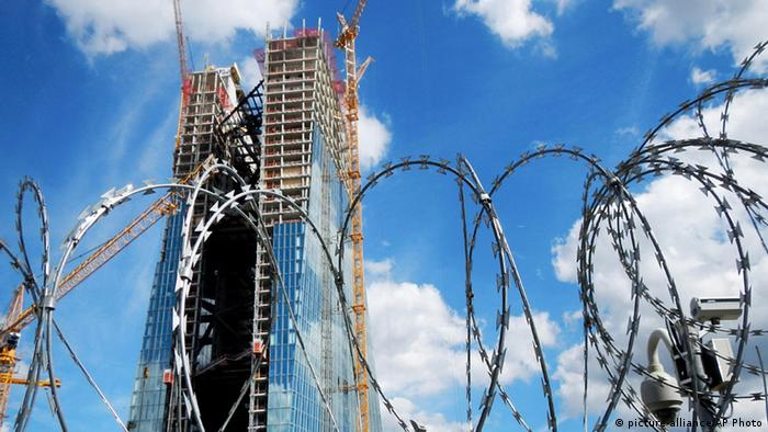 the new headquarters of the European Central Bank rises behind barbed wire in Frankfurt, Germany. (AP Photo/Michael Probst, File)