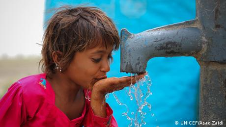A girl drinking from a water tap that is provided by UNICEF