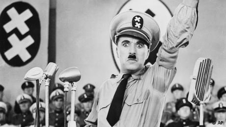 Charlie Chaplin with raised arm and a look of rage in his eyes, before microphones and not swastikas but Xs on the background wall