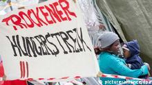 Ein Transparent mit der Aufschrift Trockener Hungerstreik hängt am 27.06.2013 in München (Bayern) in einem Zeltlager in dem Hungerstreikende, die ohne zu essen und seit drei Tagen auch ohne zu trinken für die Anerkennung ihrer Asylanträge kämpfen. Mehrere Demonstranten wurden bereits ins Krankenhaus gebracht. Foto: Marc Müller/dpa