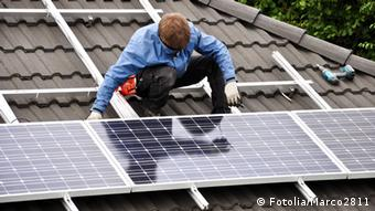 Мастер устанавливает на крыше солнечную батарею